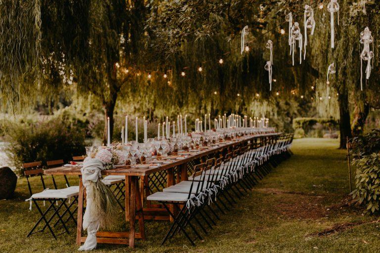 gedeckte Tafel unter Bäumen mit Lichterkette