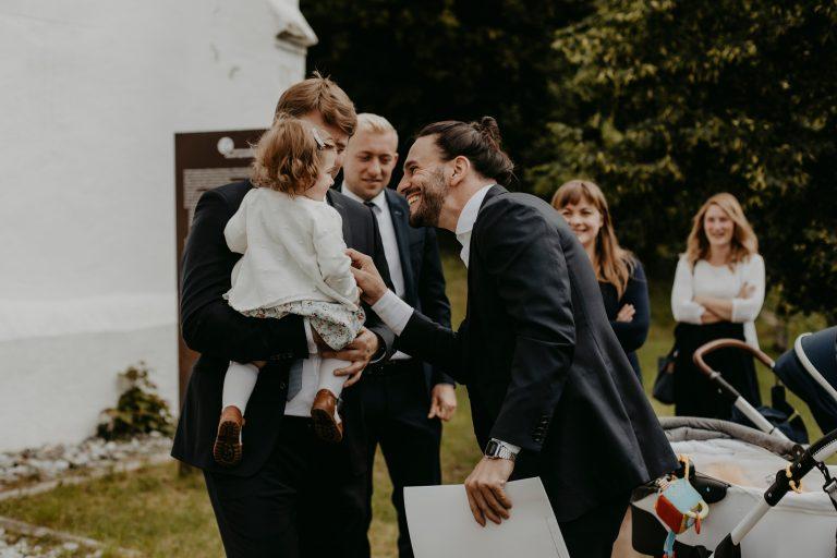 Mann begrüßt Kind, dass auf Arm von einem anderen Mann ist