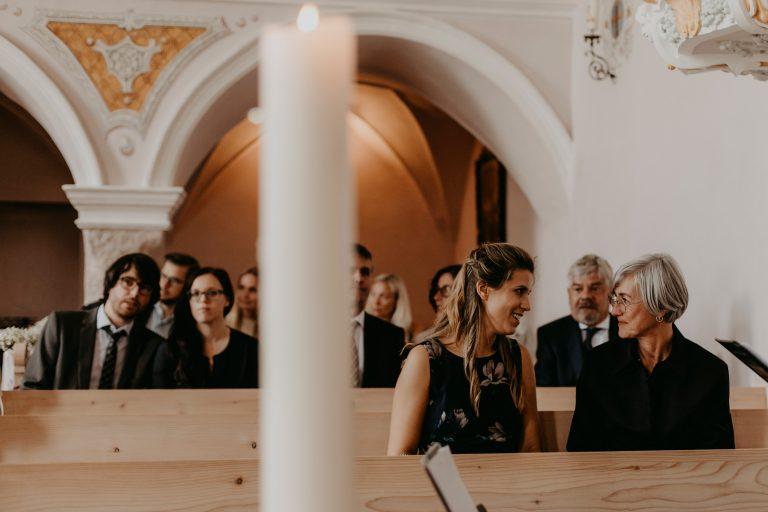 Zwei Frauen sitzen in Kirche und sprechen miteinander
