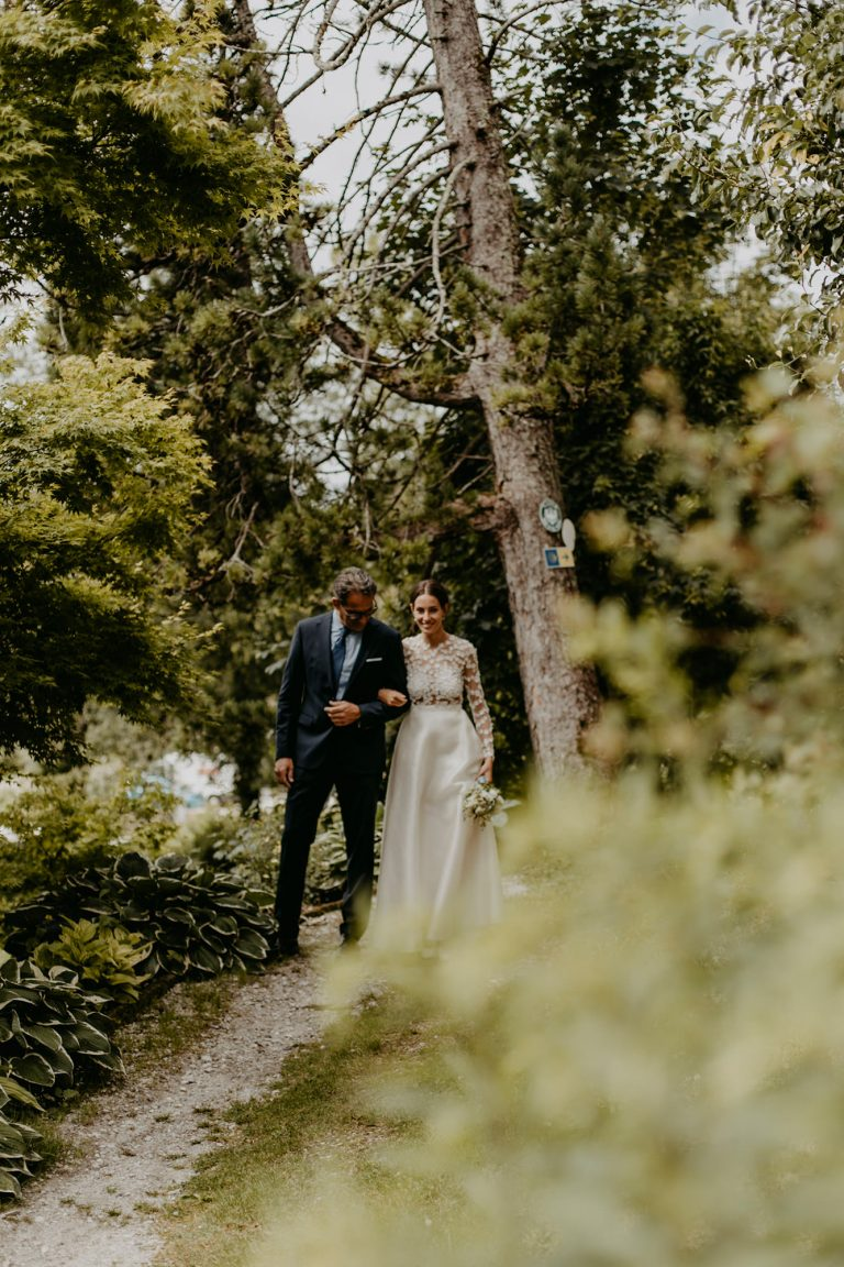 Frau in Brautkleid wird von älteren Mann durch einen Garten geführt