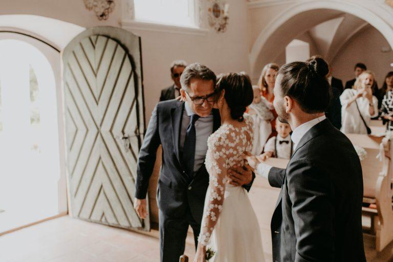 Frau in Brautkleid umarmt älteren Mann in einer Kirche