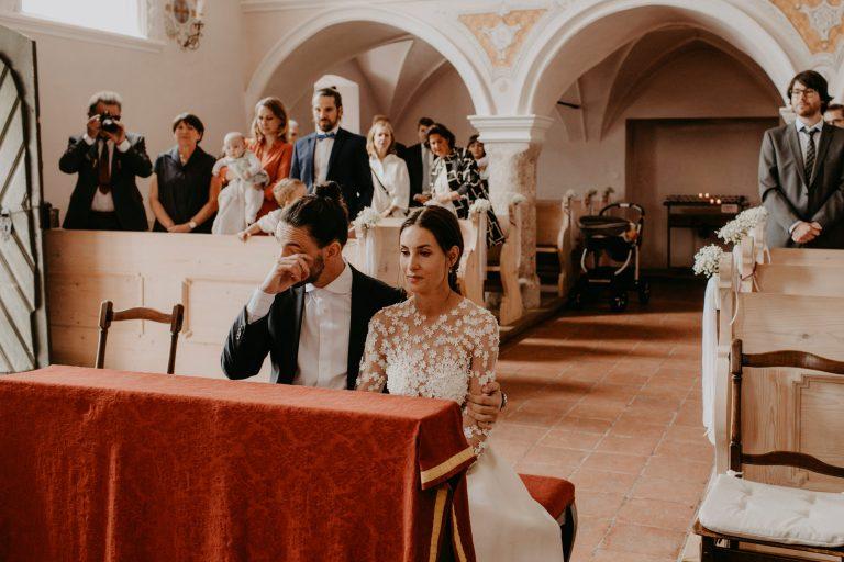 Frau in Brautkleid sitzt neben Mann im Anzug vor dem Altar