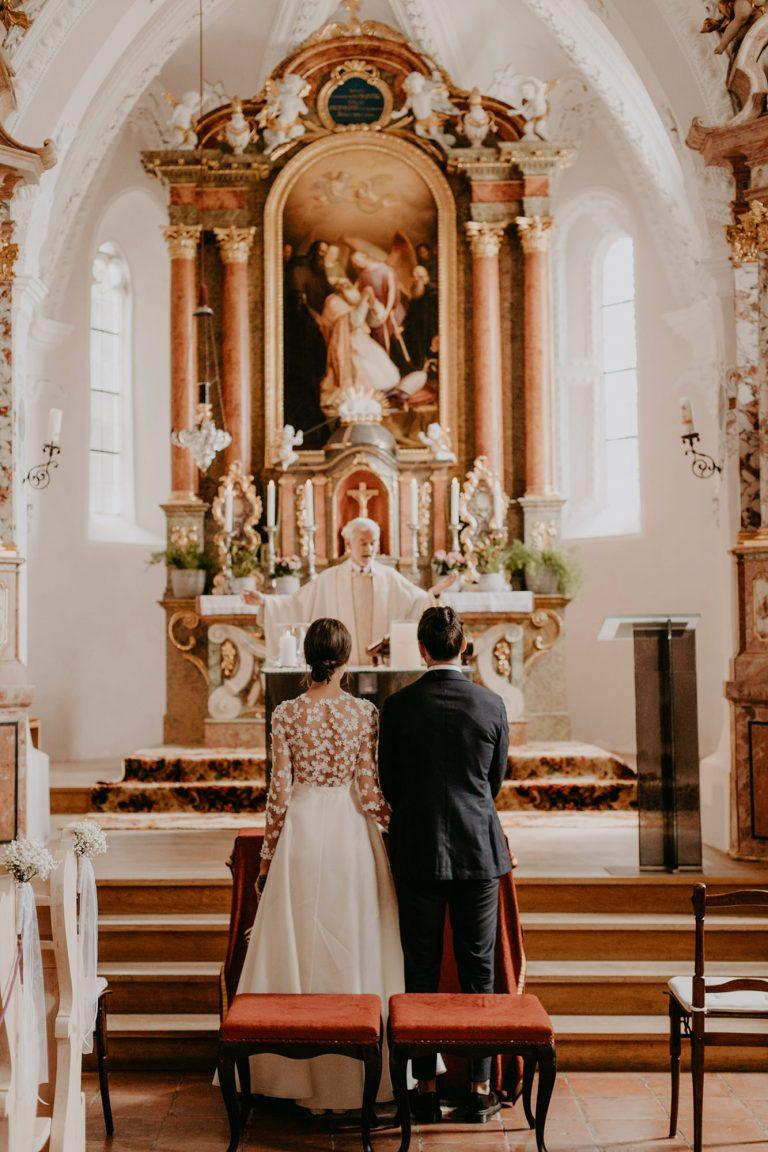 Brautpaar von hinten zu sehen vor einem Altar