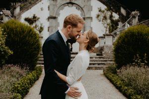 Brautpaar küsst sich vor villa