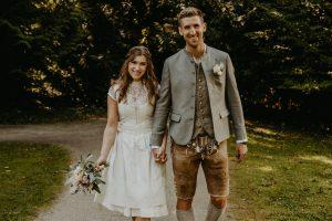 paar in Tracht mit Brautstrauß vor Wald lächelt in Kamera