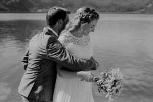 Bräutigam umarmt Braut am See